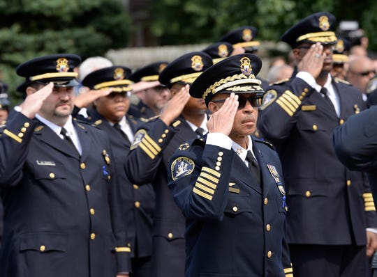 Detroit Police Chief James Craig and other officers salutes the casket of fallen officer Fadi Shukur as it leaves the funeral service at St. George Chaldean Catholic Church in Shelby Township, Mich. on August 20, 2018.