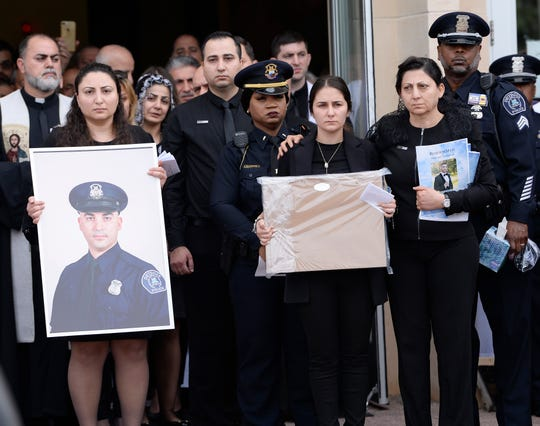 Nadeen Maroof Shukur (center), widow of officer Fadi Shukur, along with family members, watches as Fadi Shukur's casket is put in the hearse at the end of his funeral service.at St. George Chaldean Catholic Church in Shelby Township Monday.