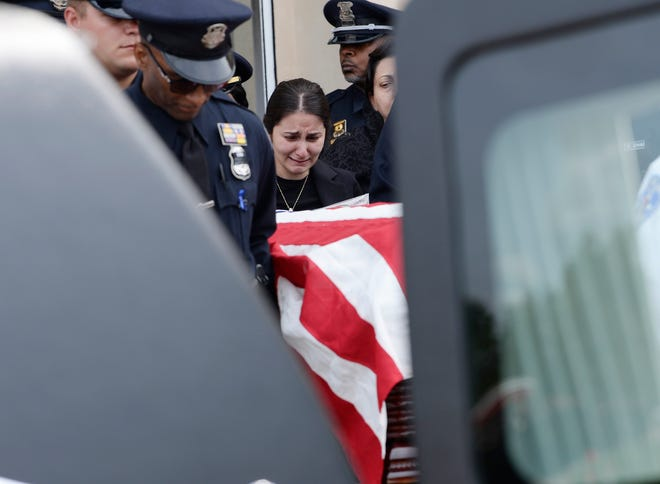 Nadeen Maroof Shukur, widow of officer Fadi Shukur cries as his casket passes her and is put inside a hearse at the end of his funeral service in Shelby Township Monday.
