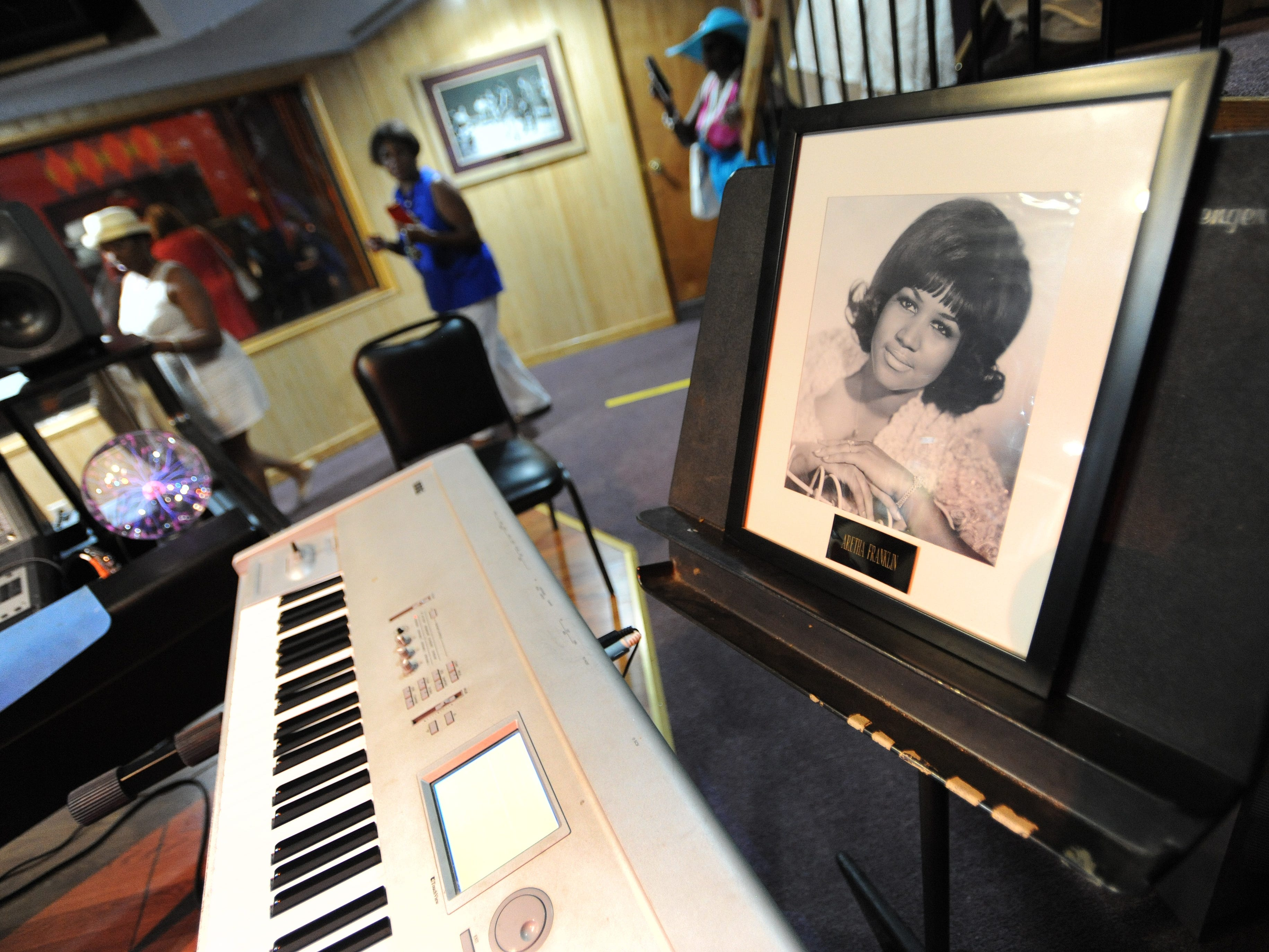 Visitors walk past a framed photo of Aretha Franklin in Studio A.