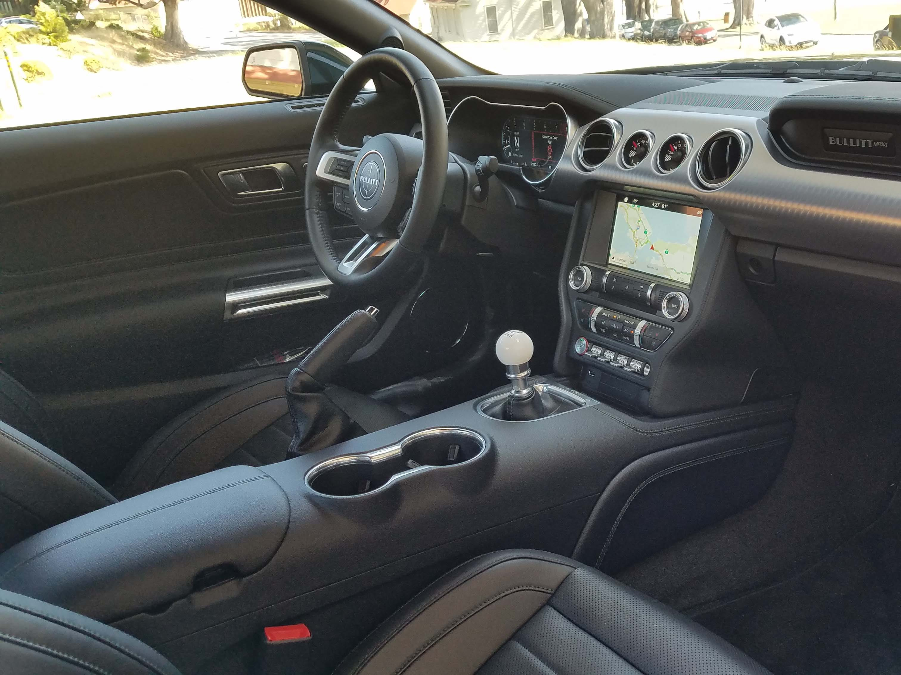 """The interior of the 2019 Ford Mustang Bullitt is nicely laid out with a stitched console and leather seats. The car comes in manual only with the signature """"cueball"""" shifter, though the movie car featured a Porsche shifter courtesy of Porsche fan Steve McQueen."""