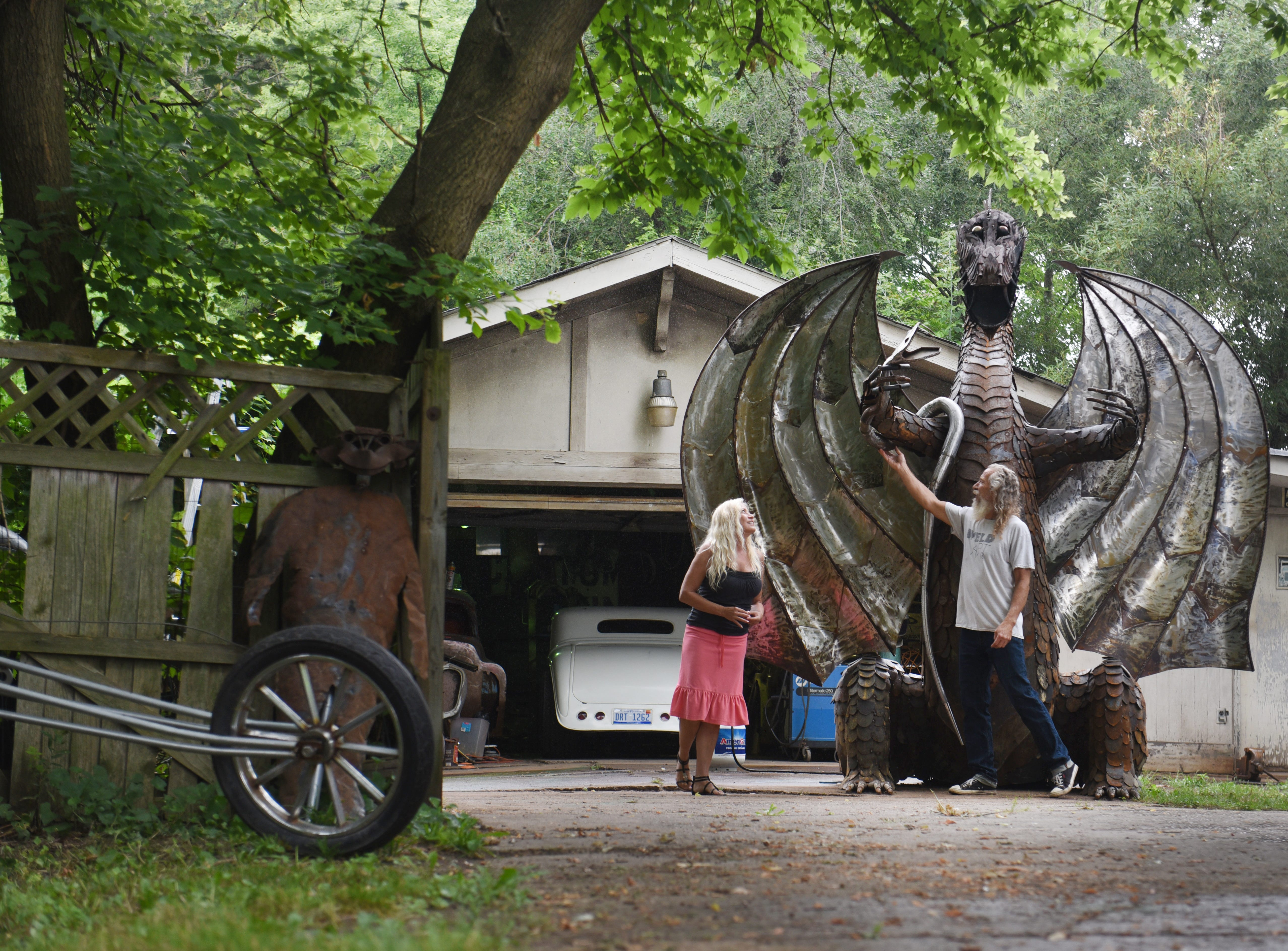 Taylor artist and metalworker Keith Coleman (right) and Suzanne Carol walk around their 12-foot fire breathing dragon metal monster