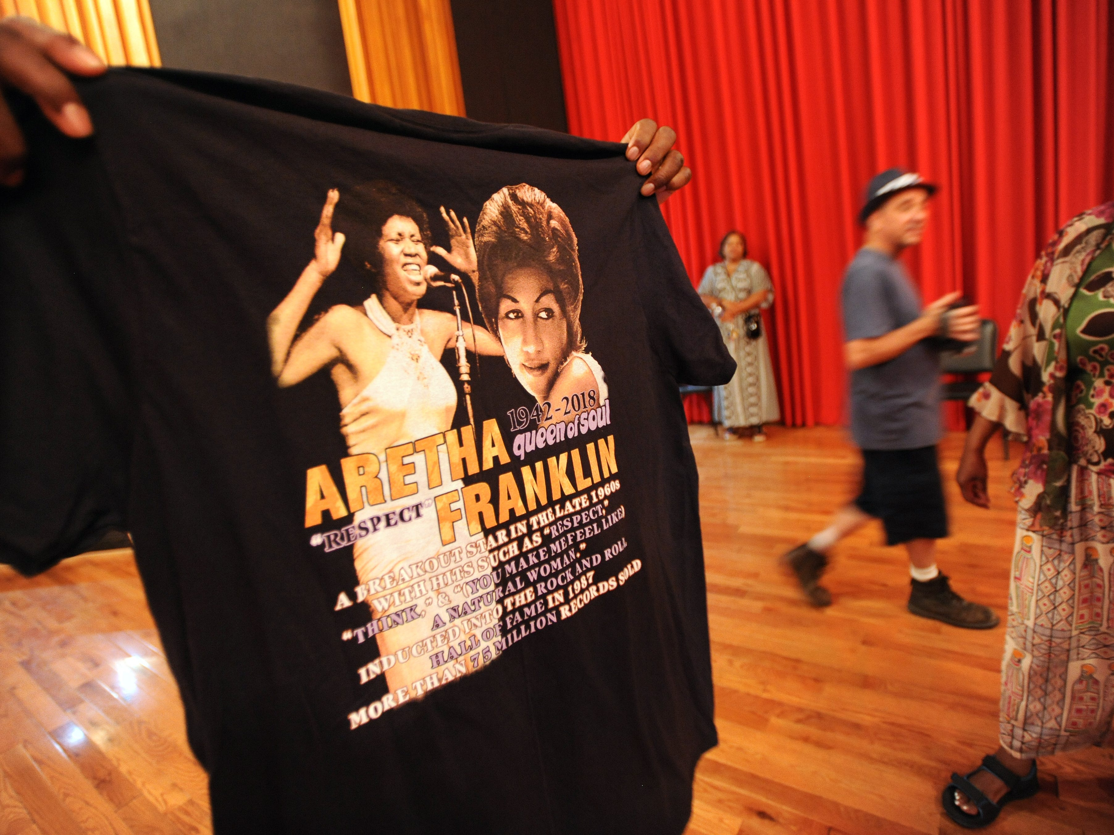 A fan proudly shows off his recently purchased T-shirt of Aretha Franklin while he was touring United Sound Systems Recording Studios.