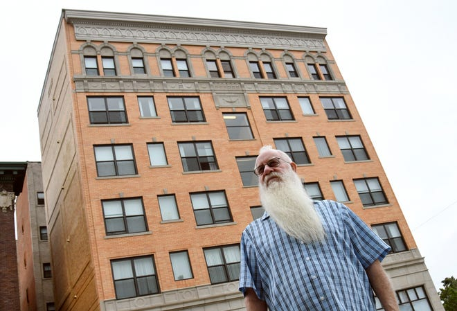 Patrick Dorn, executive director for Cass Corridor Neighborhood Development Corp., talks about Cass Plaza Apartments behind him. Empty for a few decades, it has been renovated into affordable housing.