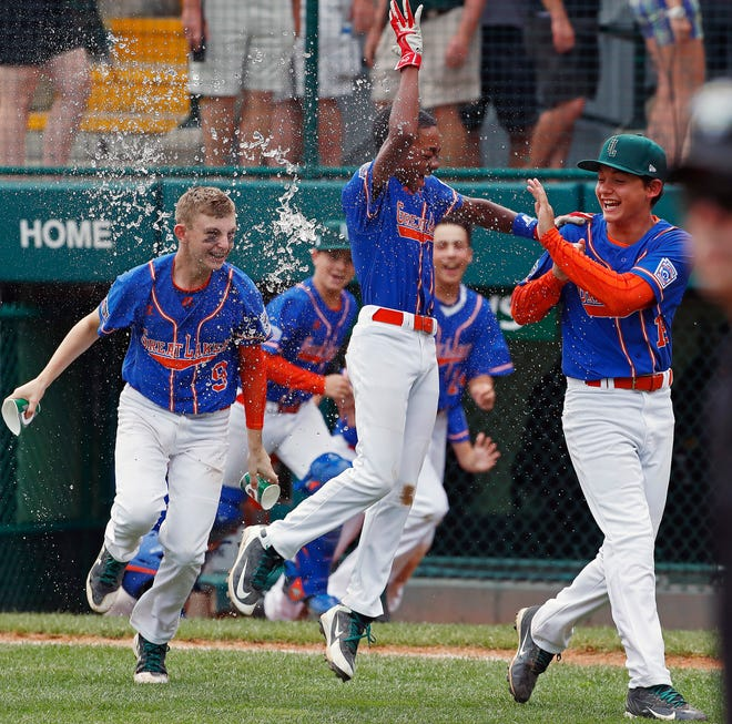 Grosse Pointe Woods, Michigan's Reggie Sharpe, center, gets a water bath from Cameron Schafer (9) as he begins to celebrate with Brennan Hill, right, after hitting a walk off single in the bottom of the sixth inning of an elimination baseball game against Des Moines, Iowa  at the Little League World Series tournament in South Williamsport, Pa., Monday, Aug. 20, 2018. Michigan won 5-4, eliminating Iowa.