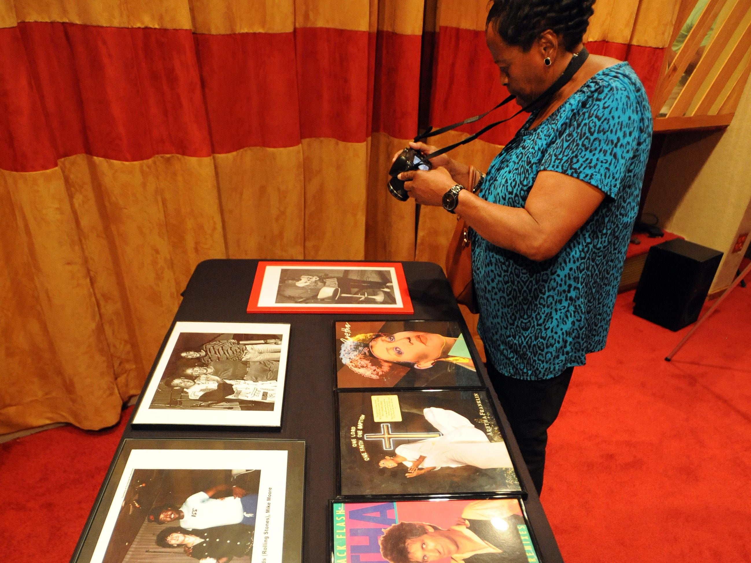 Visitors take pictures of framed photos of Aretha Franklin inside the Live Room of Studio B.