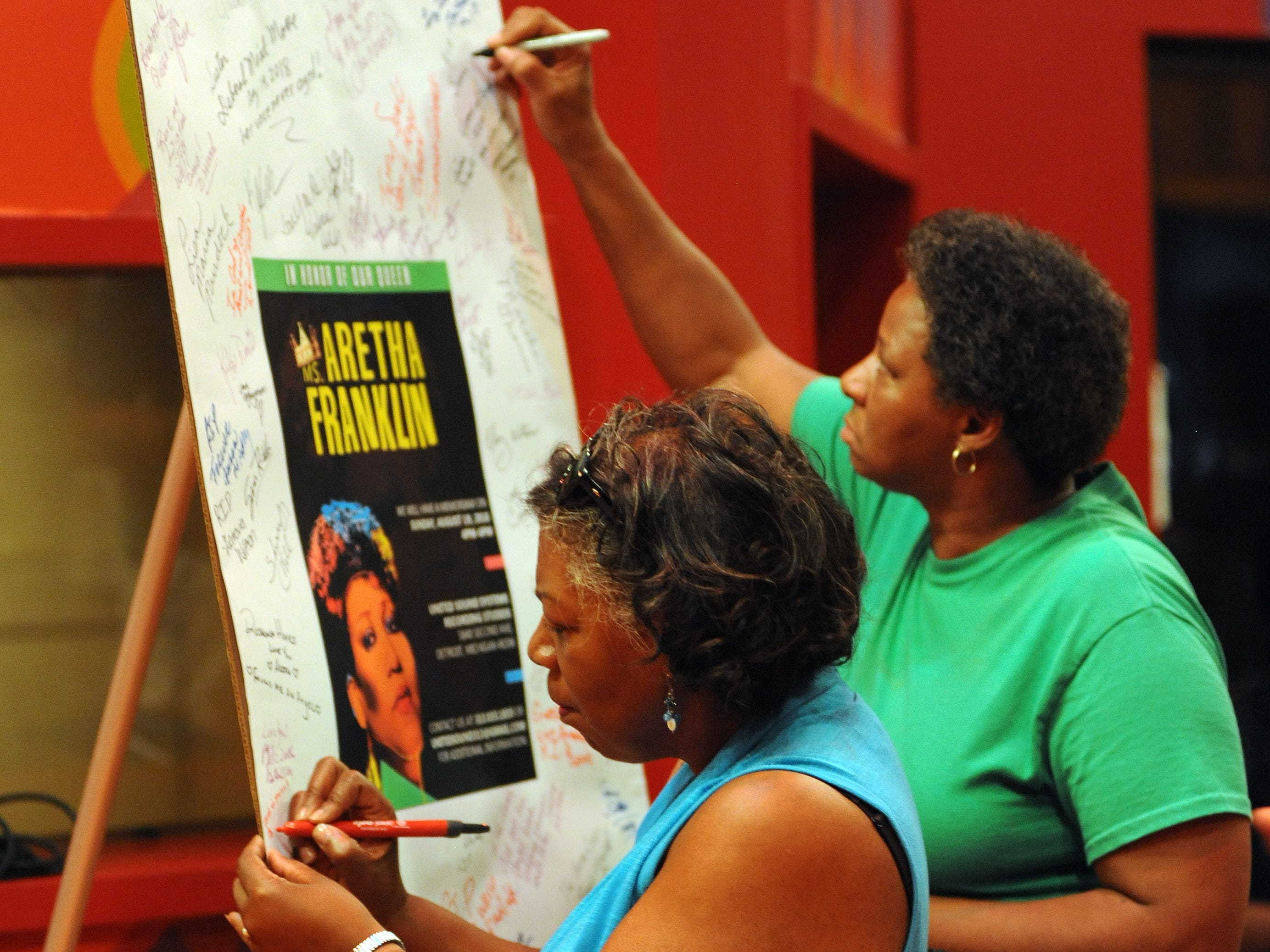 Sherry Nether of Commerce Township, Mich., signs a memorial poster of Aretha Franklin at United Sound Systems Recording Studios.