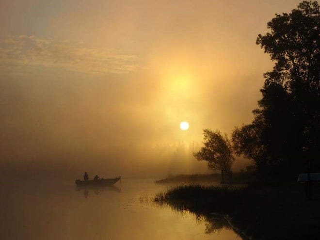 """""""Misty Fishing Morning,"""" by Diane Kanneth of Highland Park. One morning in Commerce Township, she got up early and headed down to Proud Lake, trying not to drop her coffee, granola bar and camera.  """"In that struggle,"""" she said, """"I lifted my camera in the direction of the boaters that captured my attention. The photo I quickly snapped without much expertise or thought reminds me of that one beautiful morning."""""""