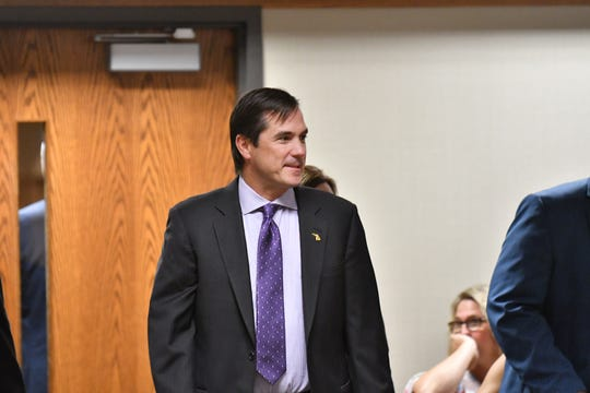 Michigan health and human services director Nick Lyon enters the courtroom before the hearing & then exits again at 67th District Court in Flint, Mich. on Aug. 20, 2018.