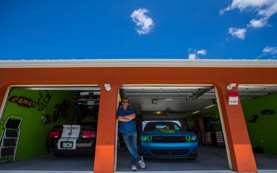"""Real estate agent Kevin Cloutier, displays his three-car garage where he established his """"man cave."""" Cloutier is also working on a project in Cape Coral, to develop a high-end man cave community geared toward Cape Coral residents who have run out of room for the toys at their house."""