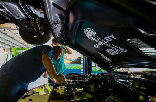 Real estate agent Kevin Cloutier,works on his Shelby Mustang stored in his three-car garage. Cloutier is also working on a project in Cape Coral, to develop a high-end man cave community geared toward Cape Coral residents who have run out of room for the toys at their house.