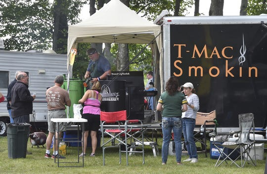 Tom MacIntosh of Sturgeon Bay, top, grills at the back end of his T-Mac Smokin' rig at last year's Death's Door B-B-Q. T-Mac Smokin' returns to try and win its third Grand Champion title at the event, having won in 2012 and '15.