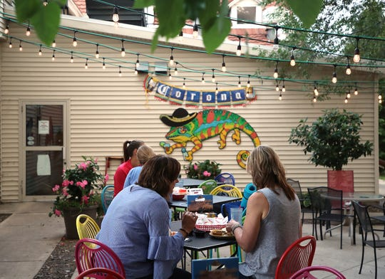 Diners relax on the patio behind Caliente in De Pere. The space has been there for a decade, but many diners are still surprised to discover it.