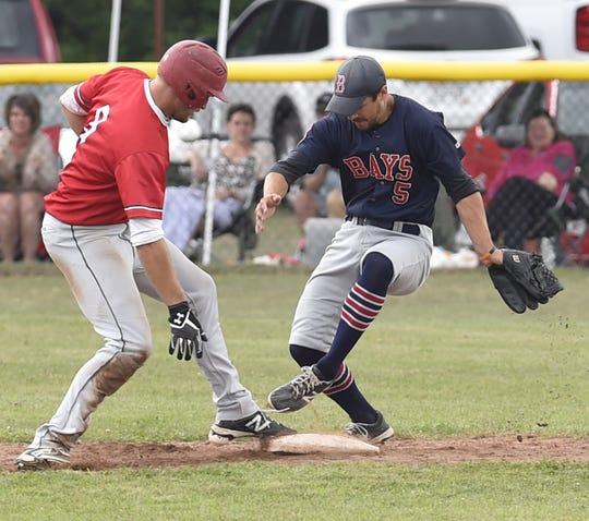 Egg Harbor's Cody Giesseman, left, beats Sister Bay's Tom Sawyer back to the base during the Door County League championship Sunday.