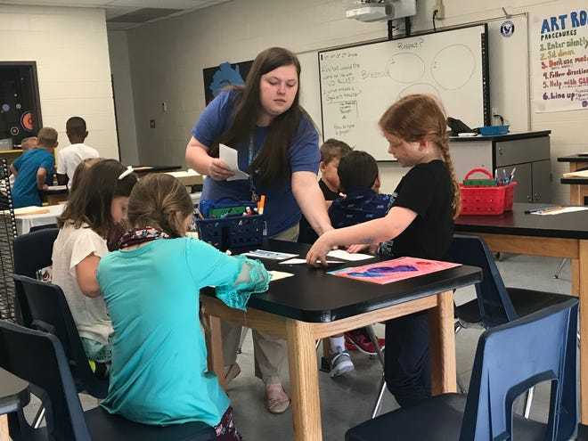 First-year art teacher Brianna Reeves works with students in her class during the first day of school at Hagood Elementary.