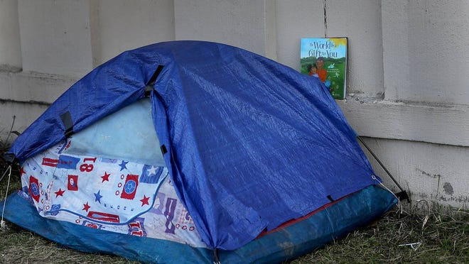 """In this photo of a homeless encampment, a child's book entitled: """"The World is a Gift to You,"""" sits on the ledge of a sound barrier wall near a tent."""