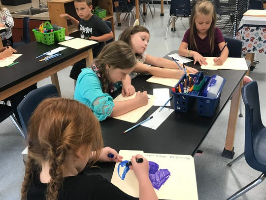 Students in new teacher Brianna Reeve's art class at Hagood Elementary work on their classwork folders.