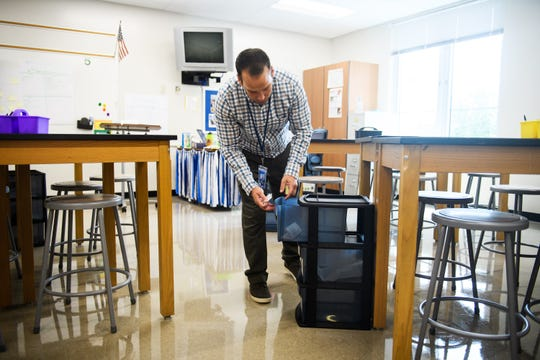 Jeff Haigler cleans up his classroom during his first day as a science teacher at Sevier Middle School on Monday, Aug. 20, 2018.