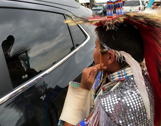 A young dancer checks his reflection at Crow Fair as he waits his turn to perform.