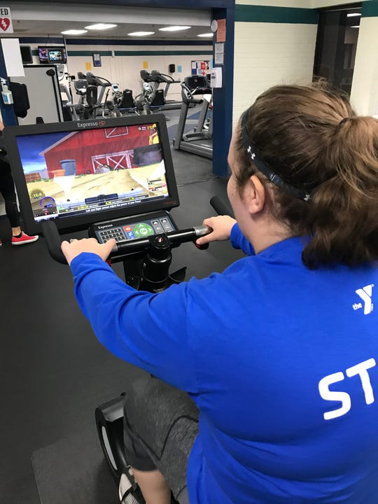 YMCA Fitness Center and Technogym coordinator Hannah Alvey performs a bike simulation designed to making biking engaging.