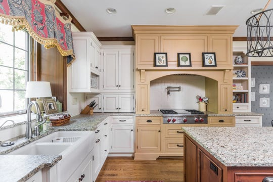 The two-tone cabinets in the kitchen were custom made to feel more like a piece of furniture. The upper cabinets sit directly on the counter tops.