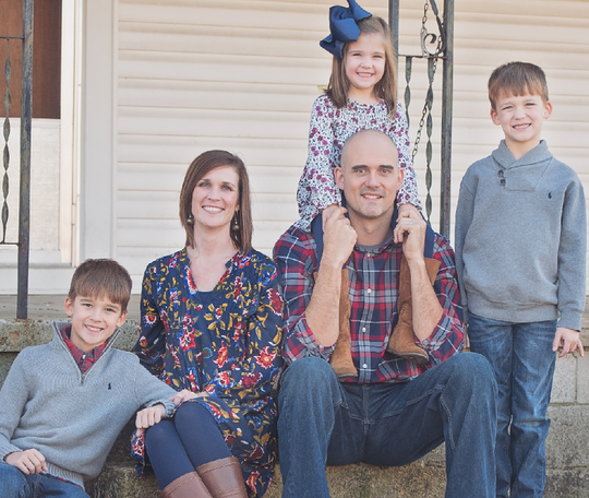 Kirk Haston (sits center), flanked by his family: (from left) Kenner, wife Kasey, Kyler (on Kirk's shoulders) and Kooper.