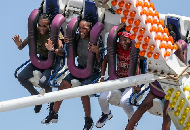 Young fair-goers scream from a swinging thrill ride on closing day of the Indiana State Fair at the State Fairgrounds in Indianapolis, Sunday, Aug. 19, 2018.