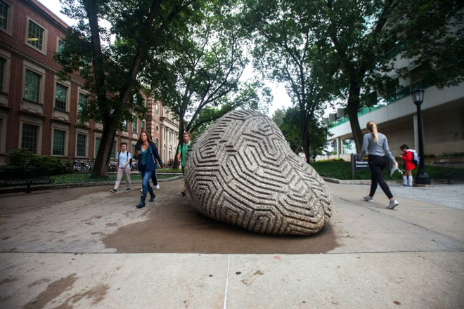 """Students walk to class past the """"Brain Rock"""" during the first day of the University of Iowa fall semester on Monday, Aug. 20, 2018, along the T. Anne Cleary Walkway in Iowa City."""