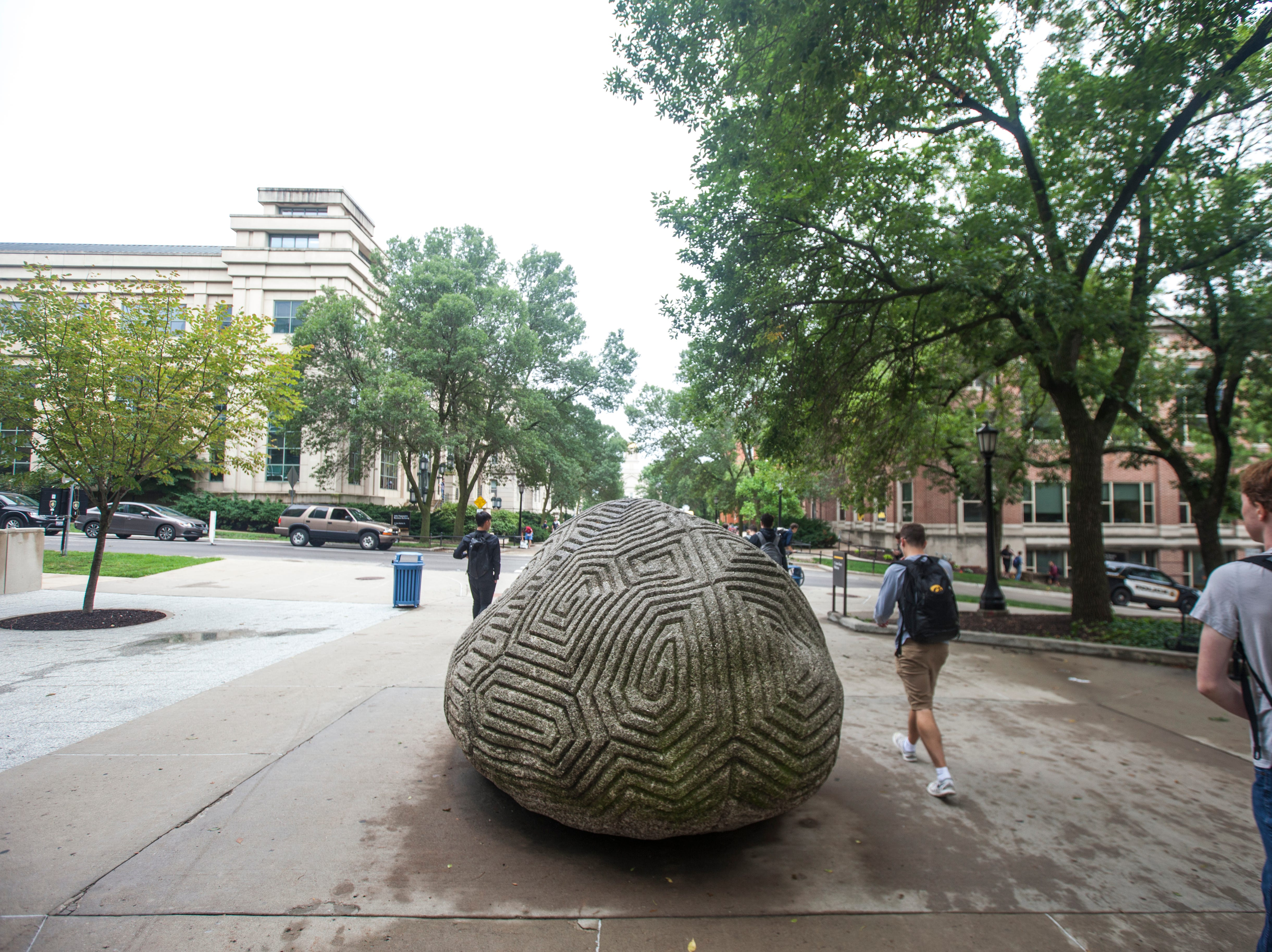 "Students walk to class past the ""Brain Rock"" during the first day of the University of Iowa fall semester on Monday, Aug. 20, 2018, along the T. Anne Cleary Walkway in Iowa City."