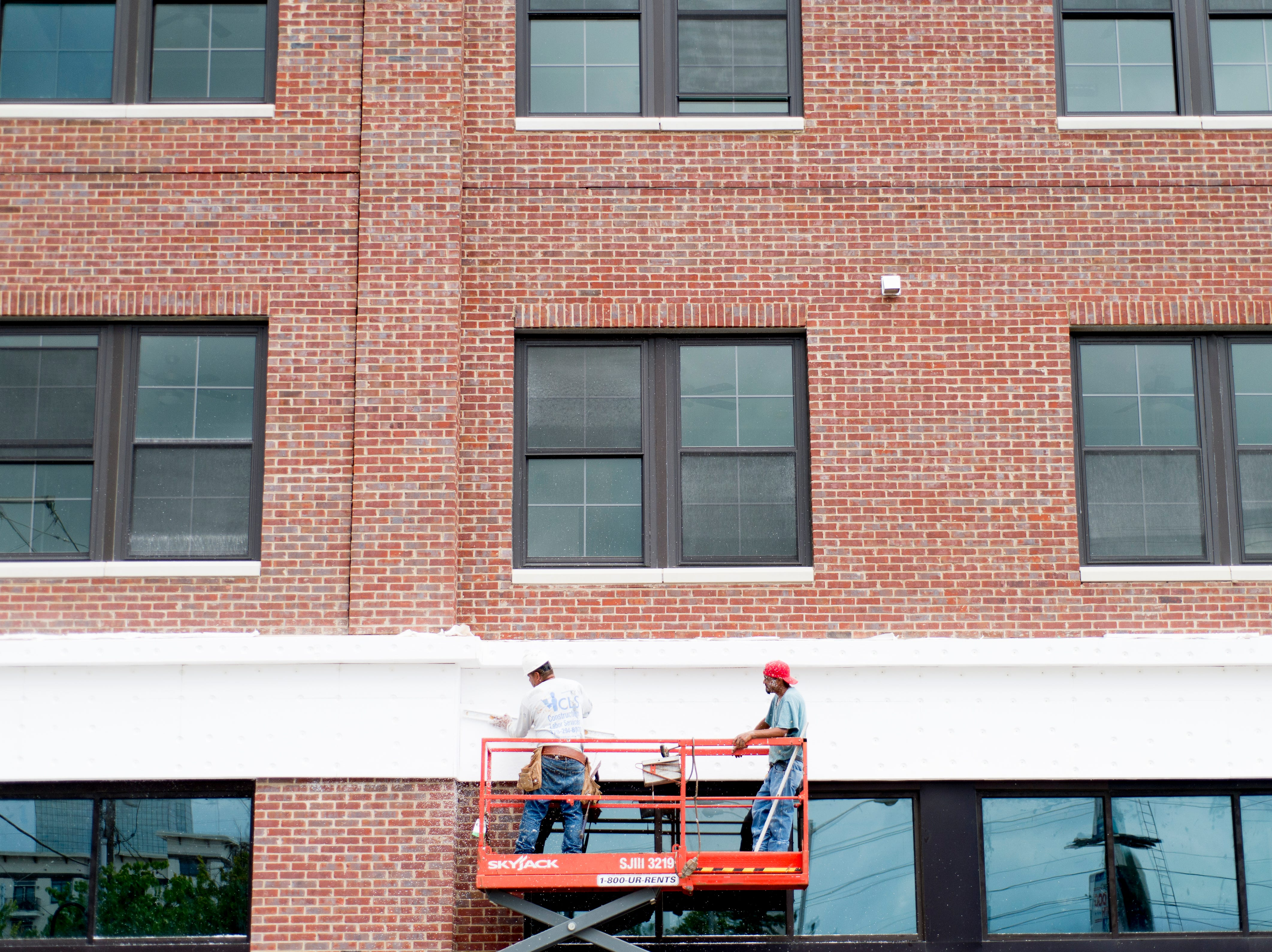 Workers construct the exterior of The Crozier in Old City in downtown Knoxville, Tennessee on Saturday, August 18, 2018.