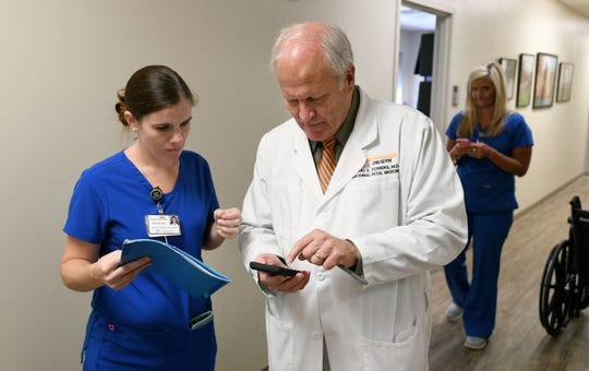 Staffer Amanda Beck checks with Dr. Craig Towers, 2018 Health Care Heroes recipient, between patients Friday, August 17, 2018.