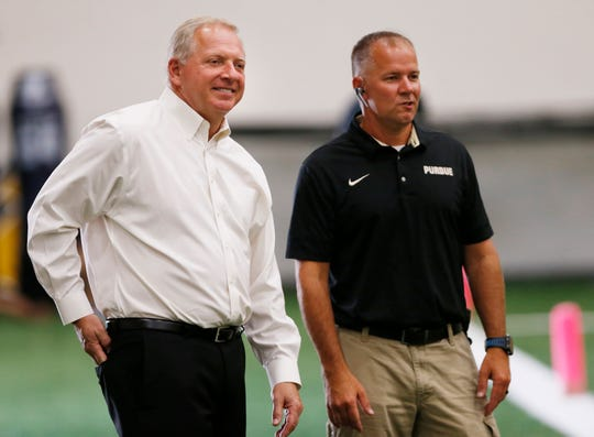Athletic director Mike Bobinski, left, and Doug Boersma, associate athletic director and director of sports medicine, share a laugh as they take in Purdue football practice Monday, August 20, 2018, inside the Mollenkopf Athletic Center.
