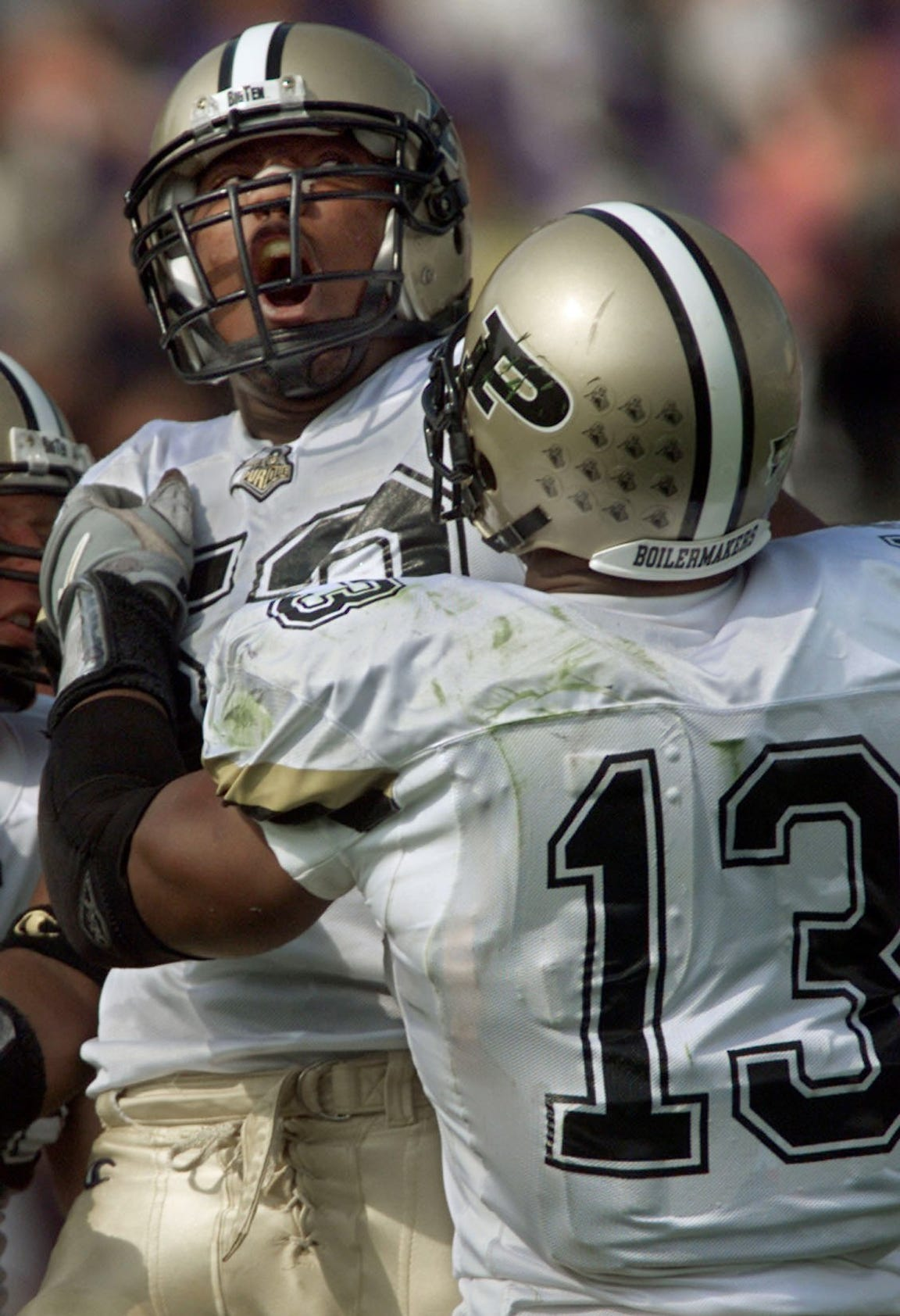 Shaun Phillips, left, is grabbed by teammate Akin Ayodele while celebrating a tackle against Northwestern in 2000.