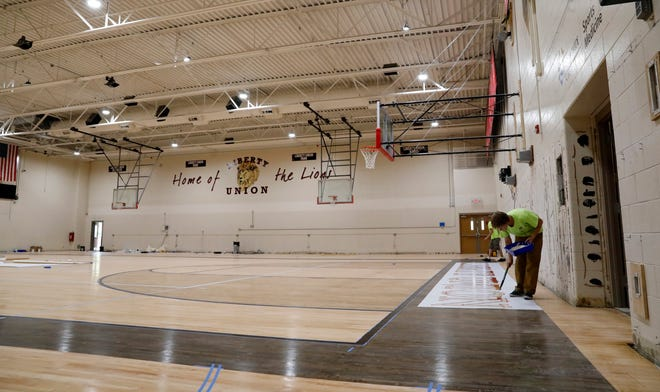 Workers paint new lettering on the recently surfaced gymnasium floor Wednesday afternoon, July 18, 2018, at Liberty Union High School in Baltimore. This summer the district has done $300,000 of improvements to the school's gymnasium, baseball and softball fields. The projects were funded through money granted to the district from the Ohio Facilities Construction Commission that had yet to be used and private donations.