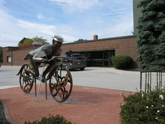 """Late for a Date"" bike rider outside the Rahr-West Art Museum in Manitowoc."