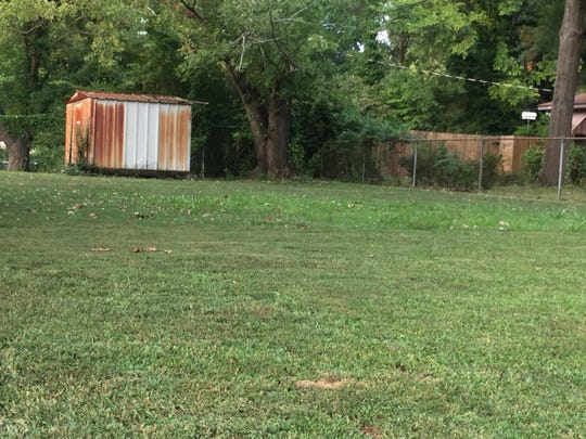 A small area of grass was left uncut in the backyard of a Frayser home where a man was shot and killed Sunday afternoon.