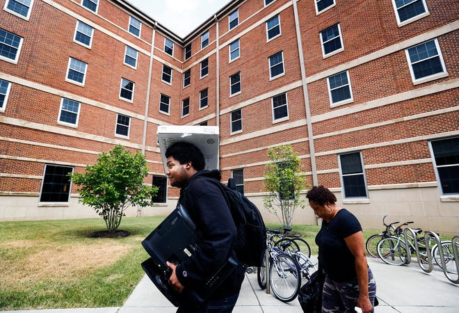 University of Memphis student Tyriq Barksdale (left) with help from his mother Tracey Barksdale (right) moves into Centennial Place residence hall for the fall semester.