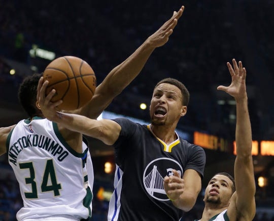 Golden State Warriors' Stephen Curry, middle, goes up for a layup between Milwaukee Bucks' Giannis Antetokounmpo, left, and Michael Carter-Williams, right, during the first half of an NBA basketball game Saturday, Dec. 12, 2015.