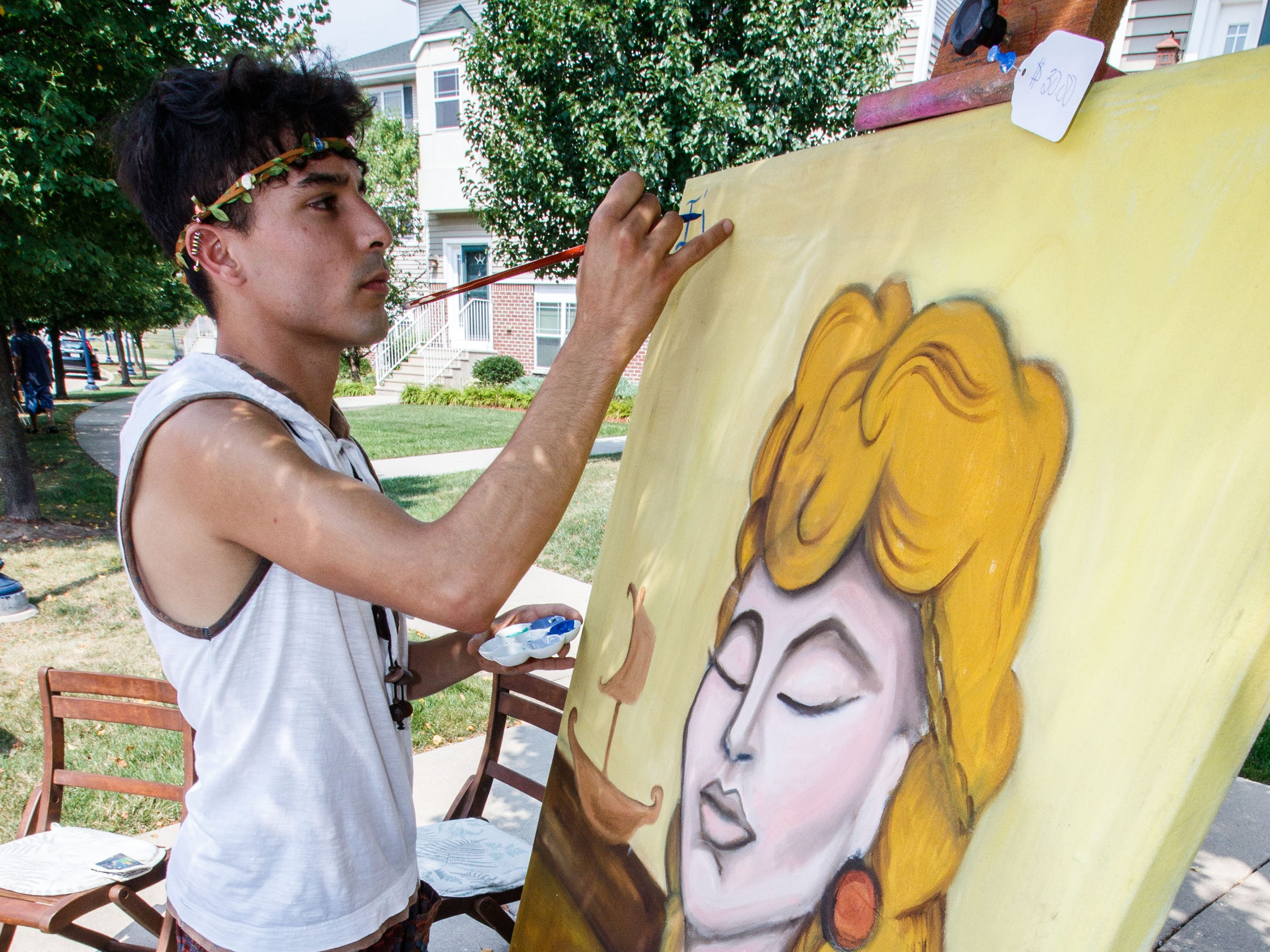 Artist Ash Ernesto of Cudahy finishes a painting during the Sunday Funday Bazaar outside the Cudahy Family Library on Sunday, August 19, 2018.