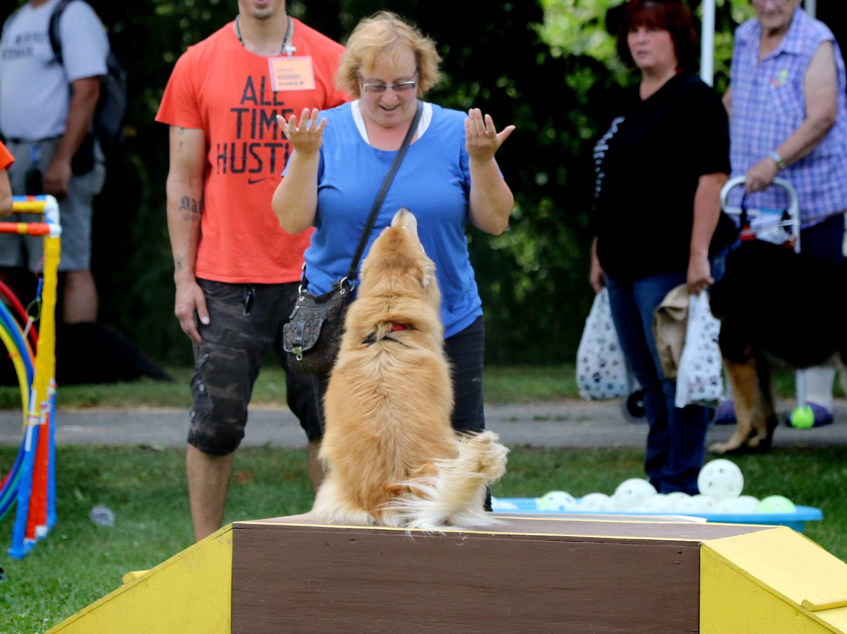 Mary Muccilli of Milwaukee gives McGiver a bit or praise after it ran the Canine Sensory Enrichment Playground during the 11th annual HAWS Pet Fair at Rotary Park in Menomonee Falls on Aug. 11.