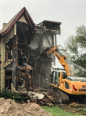 Workers use heavy equipment to demolish the historic Casper Sanger house at Catholic Memorial High School on Monday morning, Aug. 20.