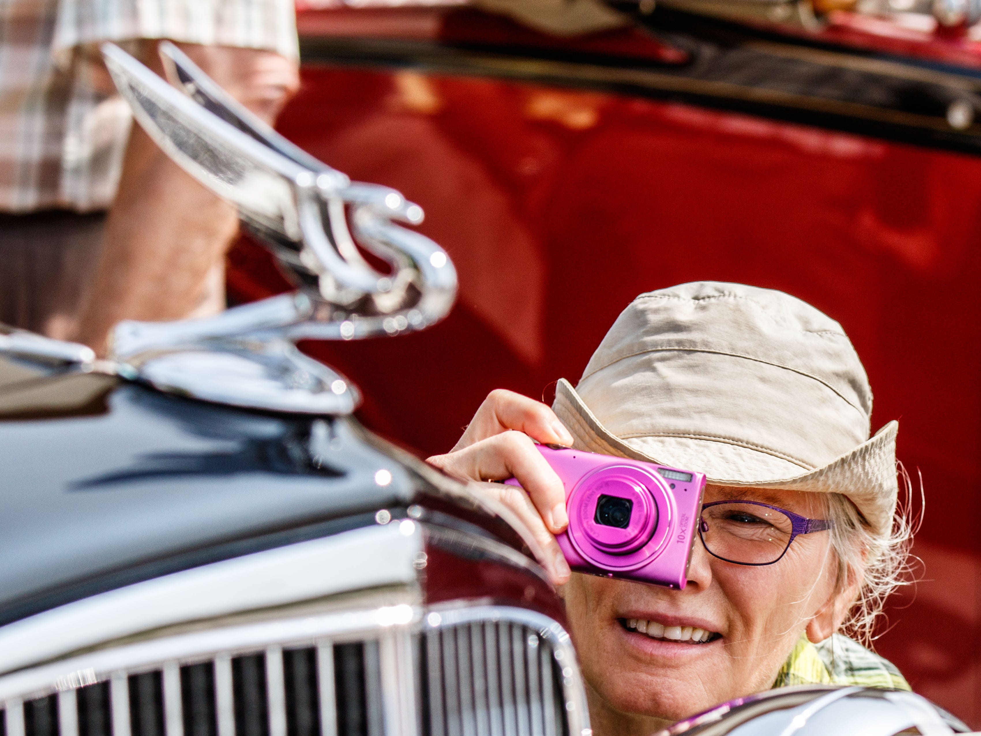 Deb Riggs of Hartland snaps a photo of the hood ornament on a restored 1934 Chevrolet Master Deluxe sedan during the 14th annual Pewaukee Antique & Classic Boat Show & Vintage Car Show on Saturday, August 18, 2018.