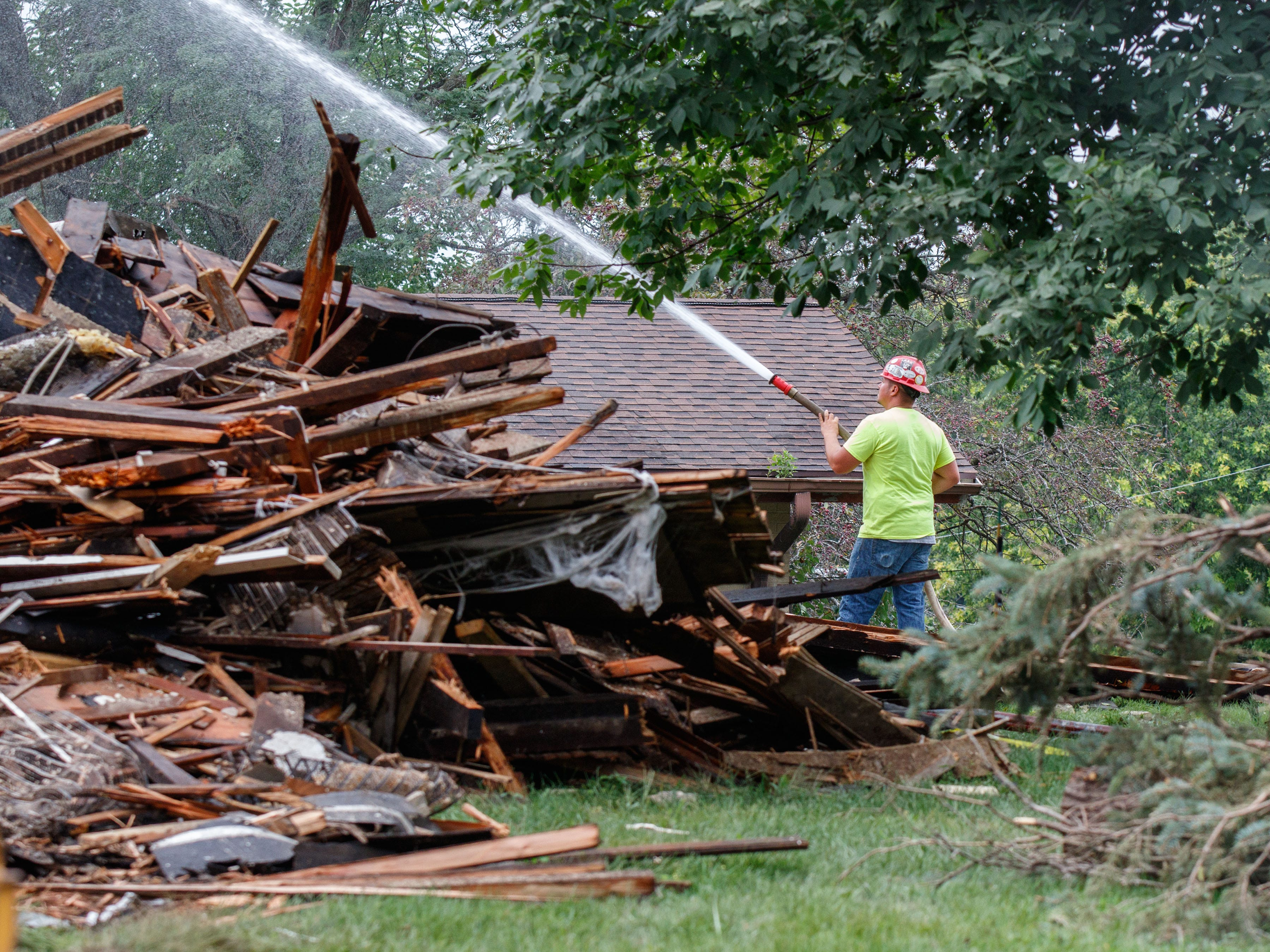 A construction worker hoses down debris after the demolition of the historic Casper Sanger house at Catholic Memorial High School on Monday morning, Aug. 20, 2018.