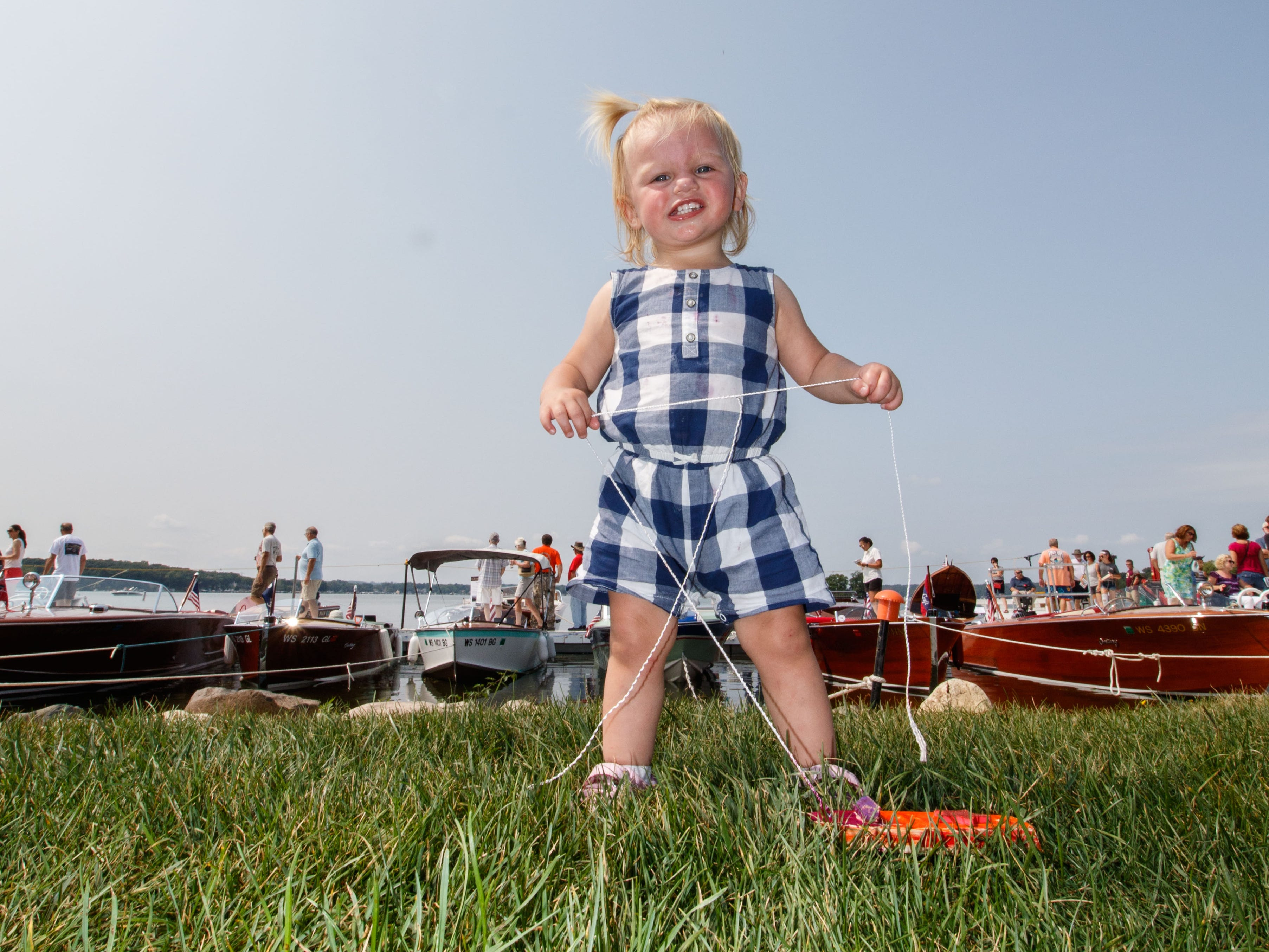 Seventeen-month-old Adley Holdmann of Pewaukee plays with a toy boat during the 14th annual Pewaukee Antique & Classic Boat Show & Vintage Car Show on Saturday, August 18, 2018.