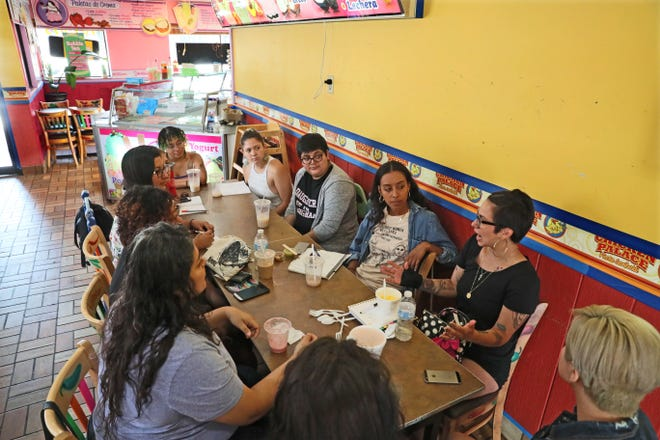 Mariah Villegas (right) takes part in a discussion with Latina artists at Chicken Palace on W. National Ave. The meeting was set up to discuss making Latina artists more visible in Milwaukee art scene.