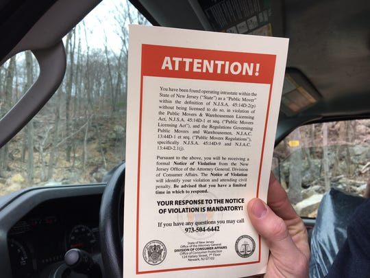 A mover reviews a copy of a notice for allegedly operating without a mover's license during a sting operation in Montville conducted by the state Division of Consumer Affairs.