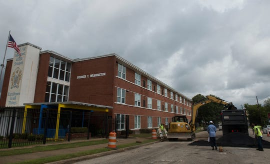 Crews work to cover the street after fixing a water main break outside Booker T. Washington Magnet High School in Montgomery, Ala., on Monday, Aug. 20, 2018.