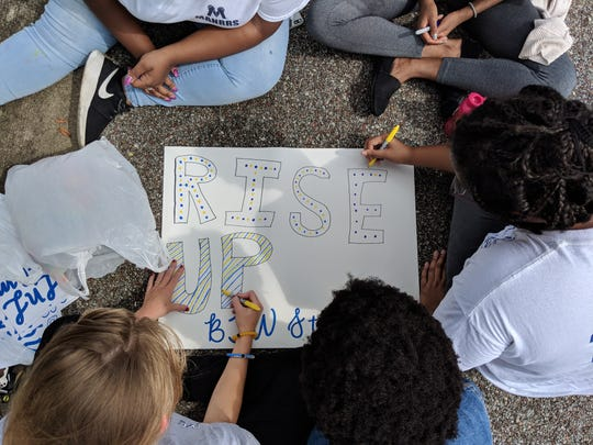Booker T. Washington Magnet High School students color a poster on Aug. 20, 2018, two days after one of the school's buildings burned down.