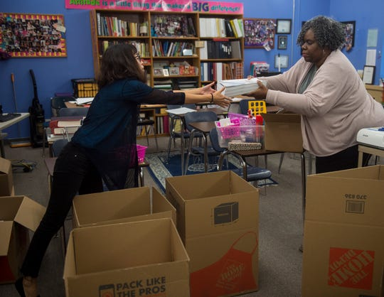 Mandarin Chinese teacher Yuan Zhang, left, and AP Language teacher Zestlan Simmons pack up Simmons classroom at Booker T. Washington Magnet High School in Montgomery, Ala., on Monday, Aug. 20, 2018. An early Saturday fire demolished one of the schools buildings forcing the entire staff and student body to move to a new location.