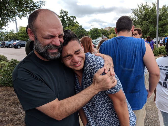 Robert Shimp (left) comforts Booker T. Washington Magnet High School student Gerson Castro on Aug. 20, 2018. A building at Castro's school burned down two days prior.